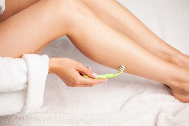 Woman with beautiful skin shaves her legs with a razor