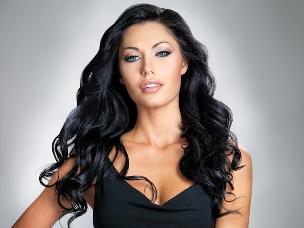 Женщина с длинными каштановыми волосами красоты - позирует в студии на сером фоне