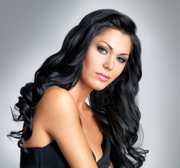 아름다움 긴 갈색 머리를 가진 여자-회색 배경에 스튜디오에서 포즈