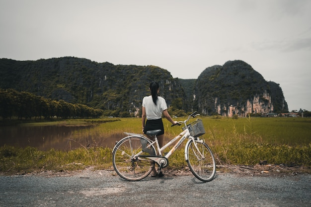 Woman with bicycle in countryside paddy field vietnam