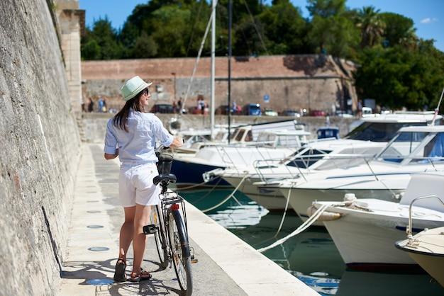 石の道に自転車を持つ女性