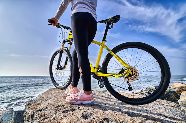 Woman with a bicycle on a shore