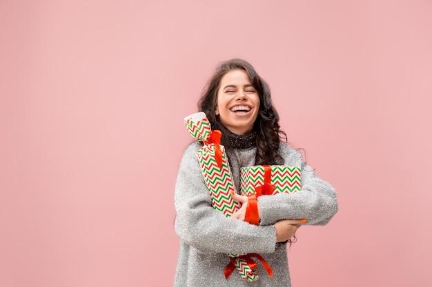 다채로운 선물 상자를 들고 큰 아름 다운 미소를 가진 여자. 부드러운 색상. 크리스마스, 생일, 발렌타인 데이, 선물. 분홍색 배경 위에 스튜디오 초상화