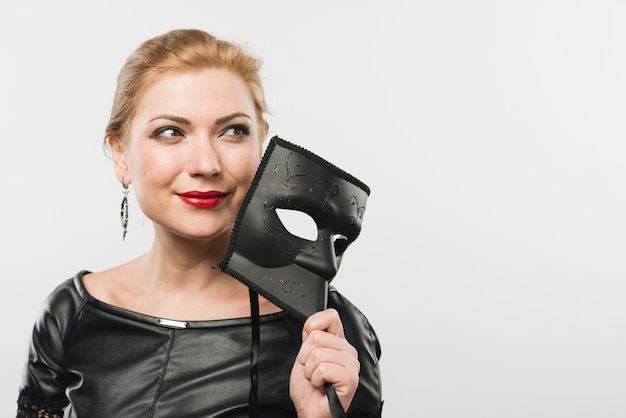 Woman with big black mask looking away