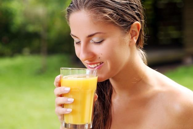 Женщина с большим стаканом свежего апельсинового сока