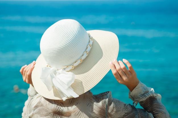 ビーチで大きな帽子をかぶった女性