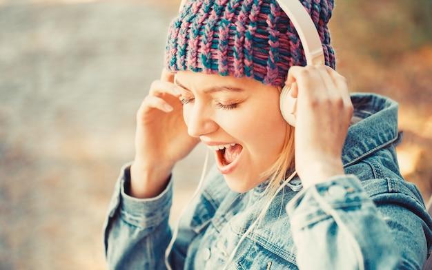 大きなヘッドホンを持つ女性。女の子はヘッドフォンで音楽を聴きます。リラックスした笑顔の女の子、音楽スマートフォンとヘッドフォン。トレンディな女の子の屋外の肖像画。秋のメロディーコンセプト。