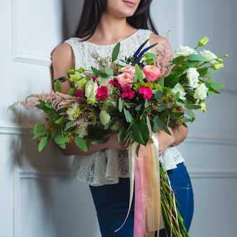 Woman with a big mixed bouquet with tulle ribbons.