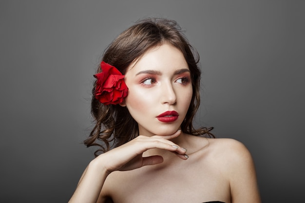 Woman with big red flower in her hair. brown-hair