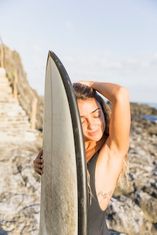 Woman with big surfboard on sea shore