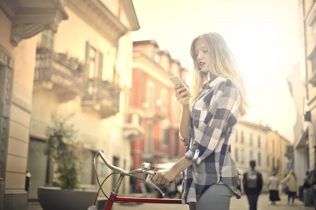 Woman with bike and smartphone