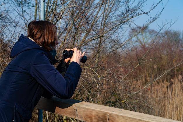 Женщина с биноклем наблюдает за птицами