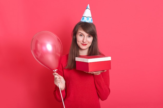 Woman with birthday cap on head, holding red balloon and present box