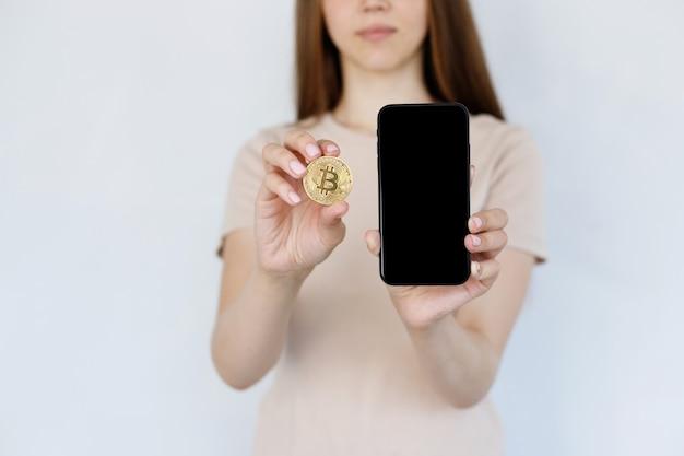 灰色の背景にビットコインと携帯電話のクローズアップの女性