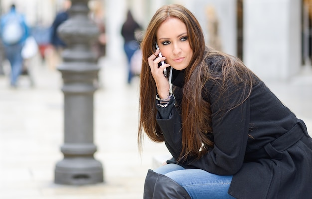 Woman with black coat using her phone