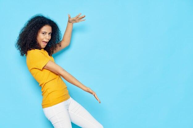 Женщина с черными вьющимися волосами эмоции жесты руками желтая футболка синяя изолированная копия пространства