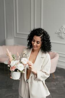 花の花束とベージュのスーツで黒い巻き毛の女性