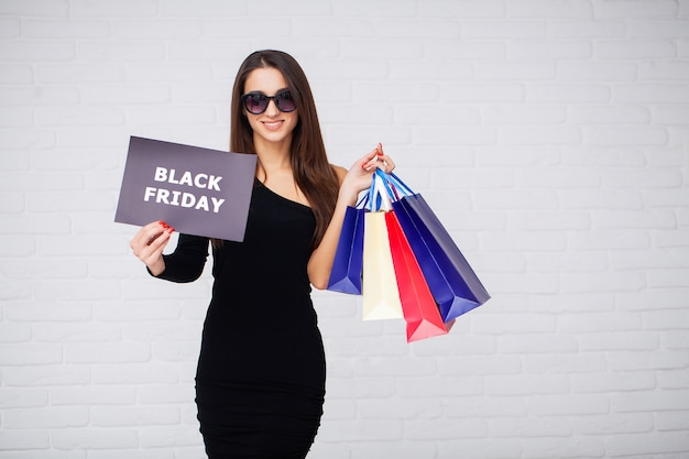 Woman with black friday inscription and shopping bags