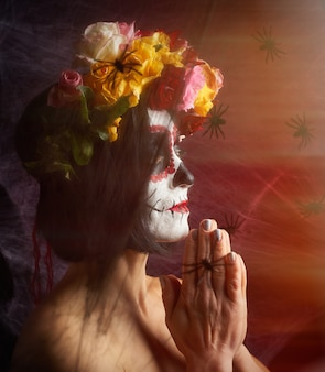 Woman with black hair is dressed in a wreath of multi-colored roses and makeup is made on her face sugar skull