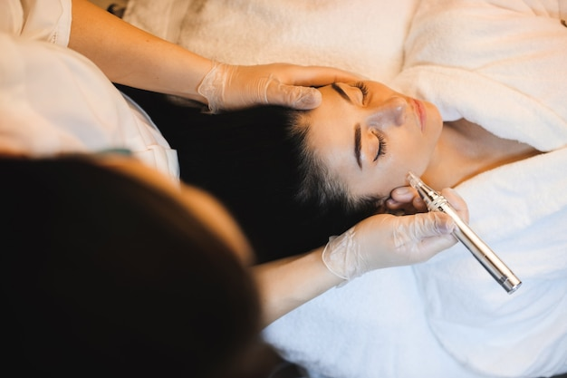 Woman with black hair is having a spa procedure for her facial skin care