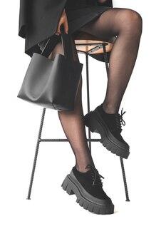 의자에 앉아 손에 검은색 핸드백을 들고 있는 여성, 흰색 배경에 격리된 검은색 팬티 스타킹 다리 클로즈업, 사업가의 개념