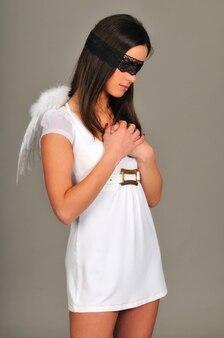 검은 레이스 눈가리개와 흰색 천사 날개를 가진 여자가 팔짱을 끼고 포즈를 취합니다.