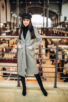 Женщина с черной кожаной кепкой, пальто и сапогами