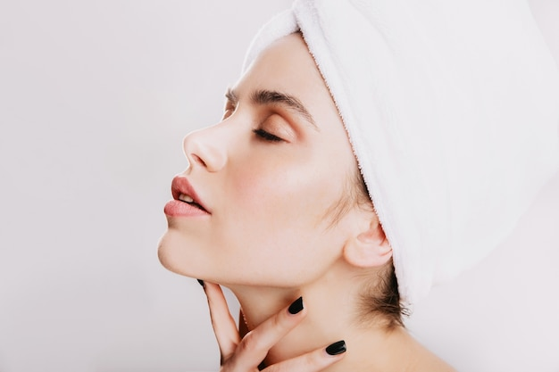 Woman with black manicure gently massages neck. portrait of young girl after shower on white wall.