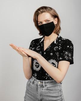 黒のシャツとマスクを持つ女性