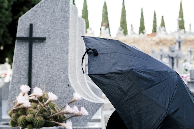Woman with black umbrella praying to loved one at the cemetery