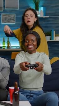 競争シミュレーションの使用中に男性の友人に対してオンラインビデオゲームをプレイしている黒い肌の女性...
