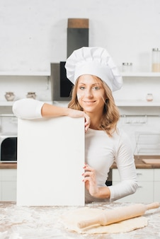 Женщина с чистым листом бумаги на кухне
