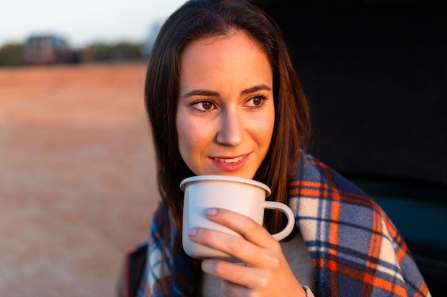 Woman with blanket on drinking coffee while admiring the sunset