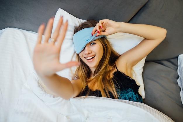La donna con la maschera benda per dormire è sdraiata sul letto al mattino.