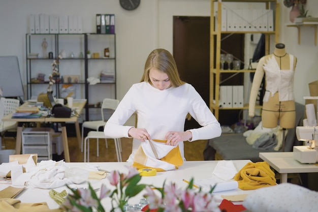 Woman with blond hair freelancer or fashion designer or tailor working on design or draft with colorful fabrics in workshop