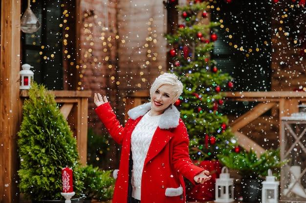 雪の下でポーズをとって赤い冬のコートを着た金髪の短い髪の女性