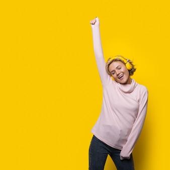 금발 머리를 가진 여자는 헤드폰을 사용하여 노란색 벽에 춤을