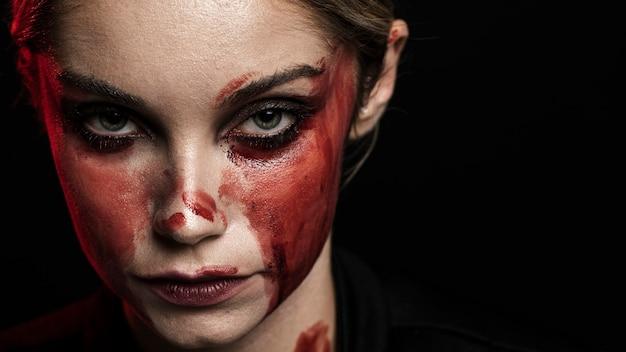 血まみれの化粧とコピースペースを持つ女性