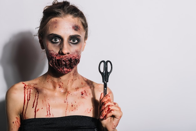 Woman with bloody sewn mouth grime and scissors
