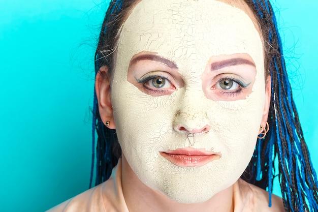 녹색 점토로 만든 냉동 마스크에 파란색 아프리카 머리띠 얼굴을 가진 여자