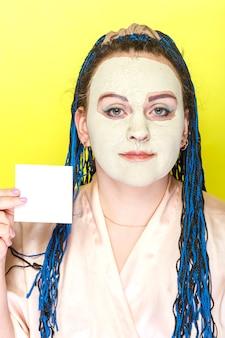노란색 표면에 그녀의 손에 명함 녹색 점토의 냉동 마스크에 파란색 아프리카 머리띠 얼굴을 가진 여자