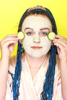노란색 표면에 그녀의 손에 오이 조각과 녹색 점토의 냉동 마스크에 파란색 아프리카 머리띠 얼굴을 가진 여자