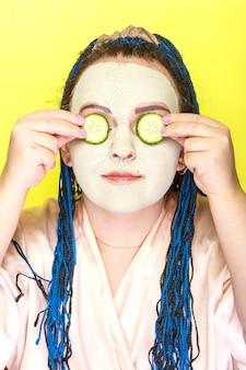 파란색 아프리카 머리띠를 가진 여자는 노란색 표면에 그녀의 눈 앞에 오이 조각과 녹색 점토의 냉동 마스크에 얼굴