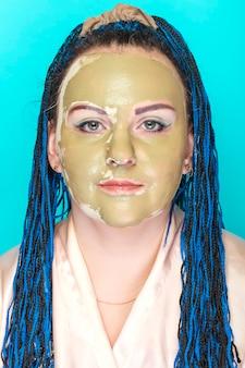 青い背景に緑の粘土で作られたマスクで青いアフロ三つ編みの女性の顔。縦の写真