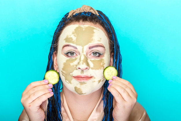 青いアフロブレードを持つ女性は、青い背景に彼女の手にキュウリの円を持つ緑の粘土で作られたマスクに直面しています。横の写真