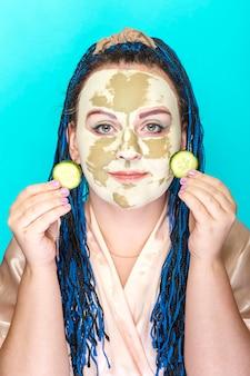 파란색 배경 세로에 그녀의 손에 오이 동그라미와 녹색 점토로 만든 마스크에 파란색 아프리카 머리띠 얼굴을 가진 여자 photo