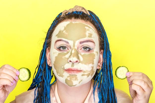 노란색 벽에 그녀의 손에 오이 동그라미와 녹색 점토로 만든 마스크에 파란색 아프리카 머리띠 얼굴을 가진 여자