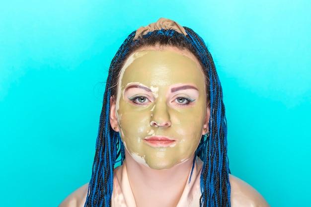 파란색 배경에 녹색 점토 마스크에 파란색 아프리카 머리 띠 얼굴을 가진 여자. 가로 사진