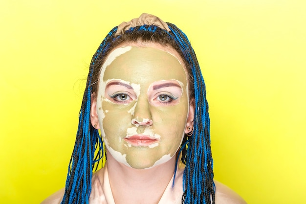 노란색 벽에 녹색 점토 마스크에 파란색 아프리카 머리 띠 얼굴을 가진 여자.