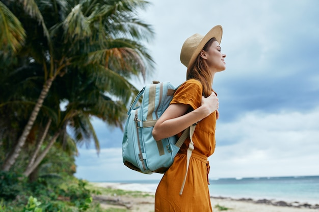 A woman with a blue backpack in a yellow dress and hat walks along the ocean along the sand with palm trees
